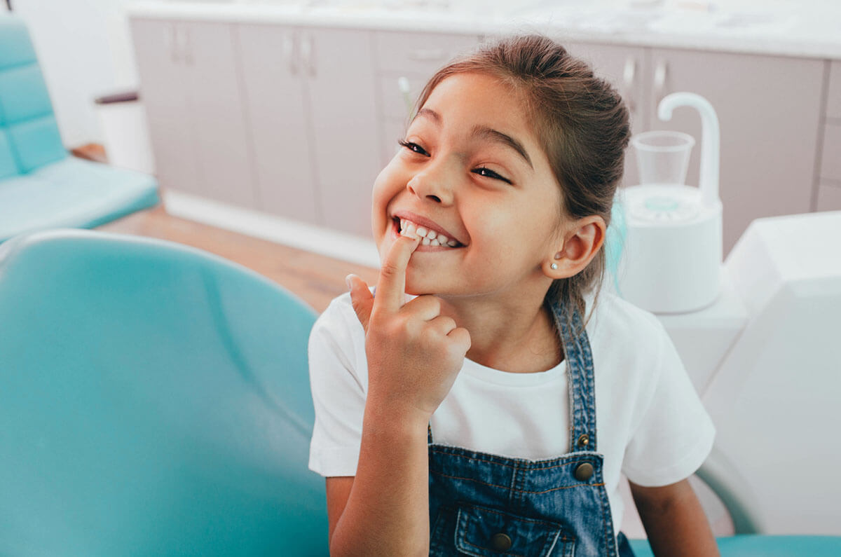 Happy little girl pointing at her healthy teeth in dentist office