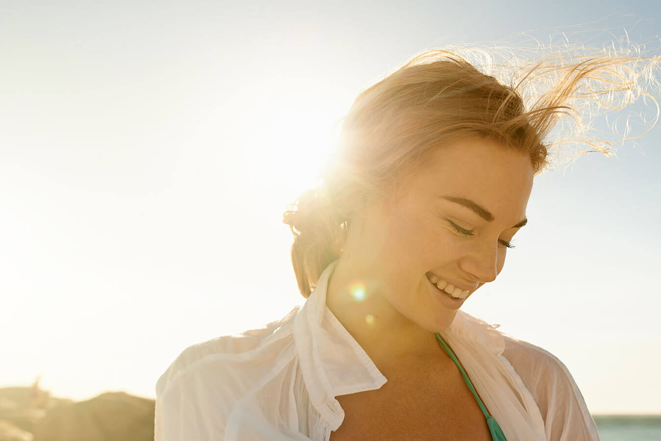 smiling woman with sun behind her