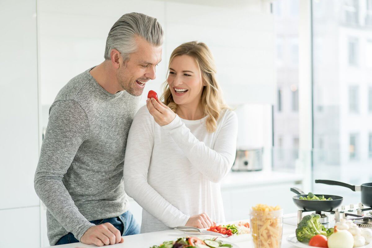 couple laughing while preparing meal together
