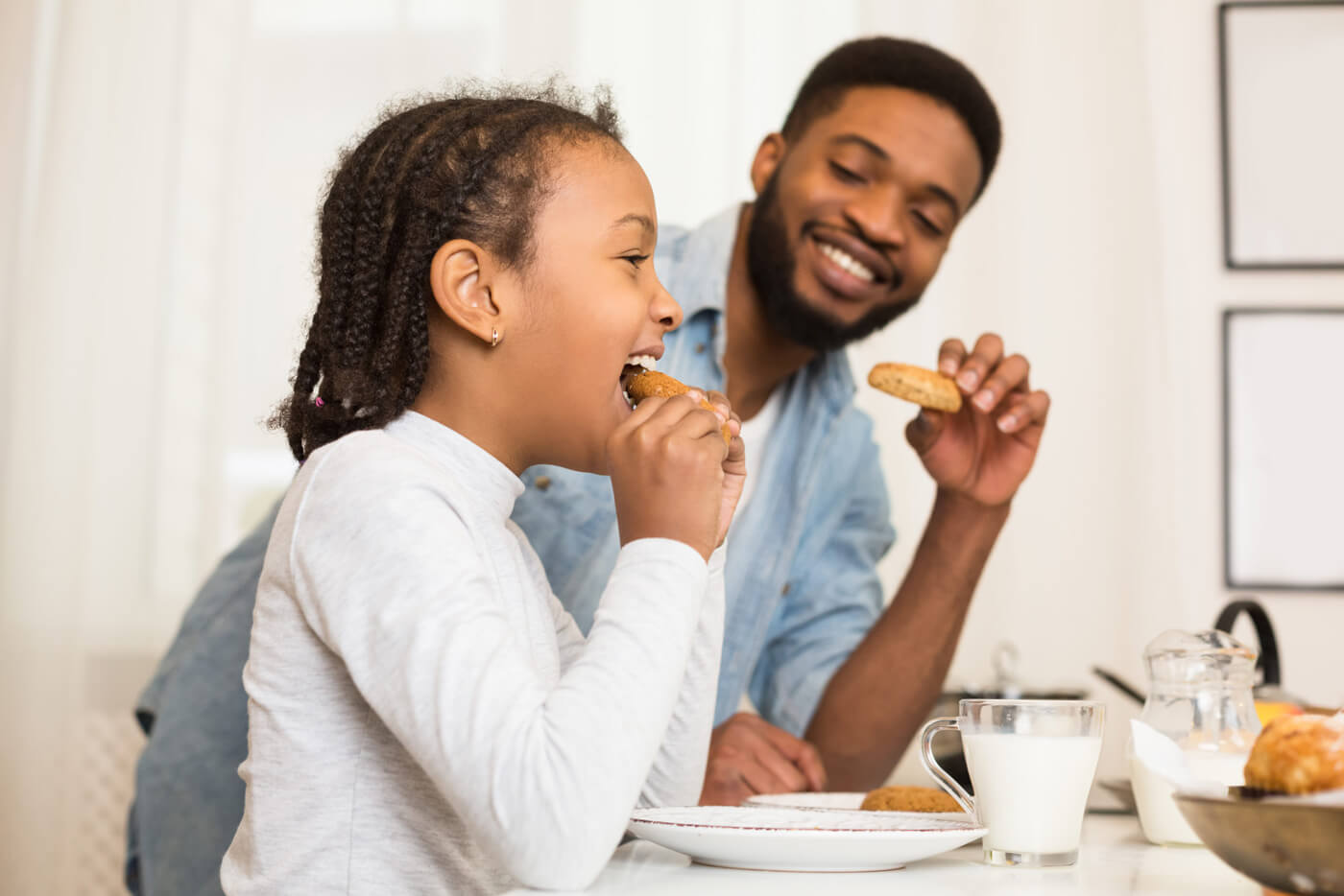 parent and child enjoying cookies in kitchen
