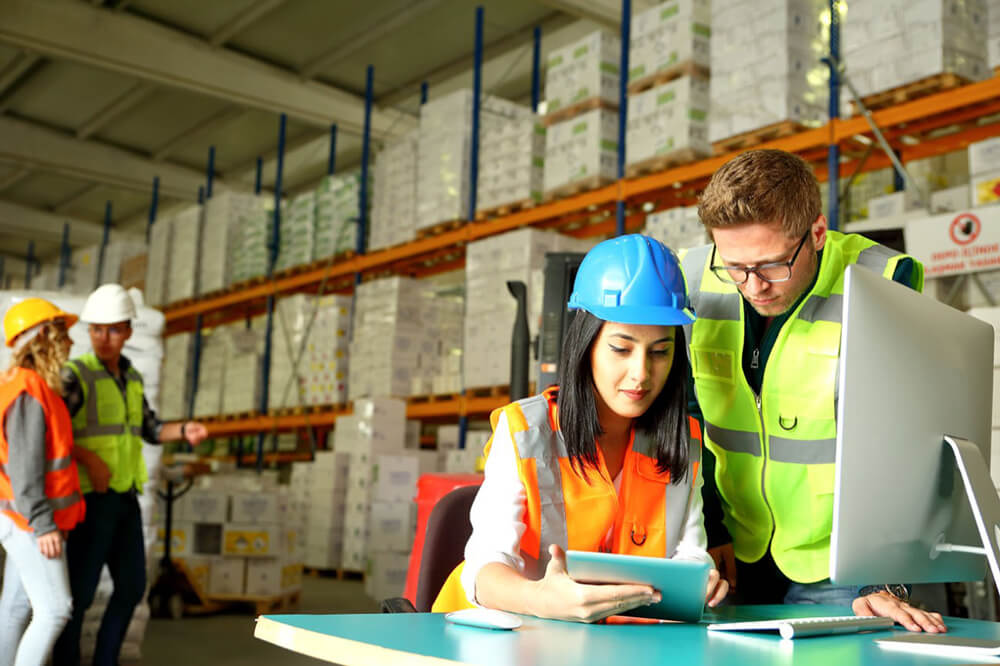 warehouse personnel checking information on a tablet